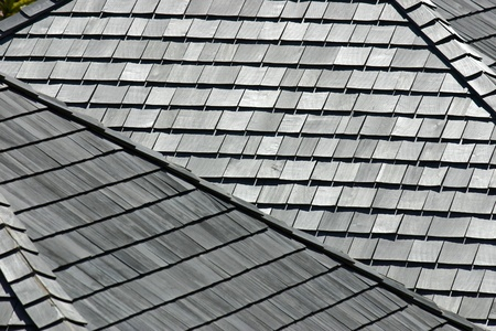 roof shingles: Several angled rooftops with worn and weathered wooden shingles