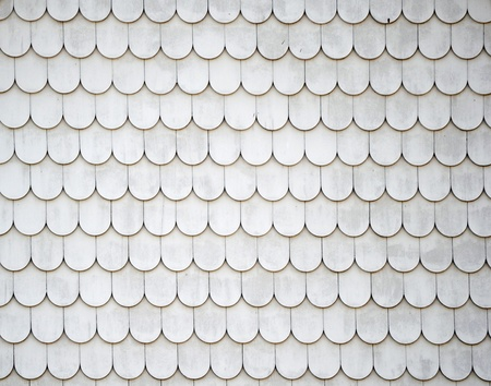 Many rounded shingles on the outside wall of a building photo