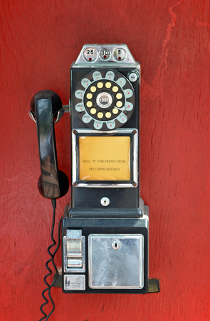 An old fashioned pay phone against a red background photo