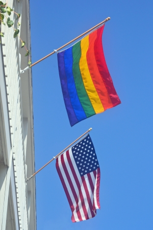A gay pride and American flag against a blue sky photo