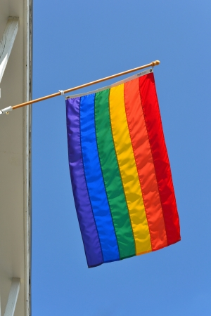 A gay pride flag waving in the wind against a background of blue sky Stockfoto
