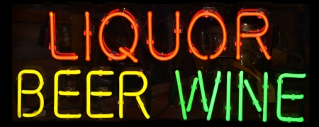 A multi colored neon sign reading Liquor Beer Wine Stockfoto