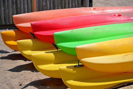 Two rows of colorful kayaks on the beach photo