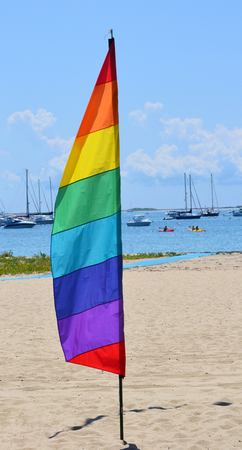 A gay pride feather flag against the background of a marina in Provincetown, Massachusetts photo