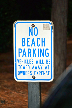 A blue and white sign that reads No Beach Parking photo