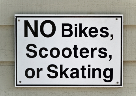 A black and white sign that reads No Bikes, Scooters, or Skating Фото со стока