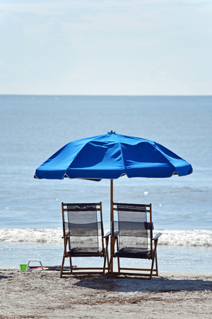Two empty beach chairs alone by the ocean photo