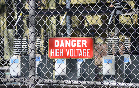 A red sign reading DANGER HIGH VOLTAGE at an electrical substation photo
