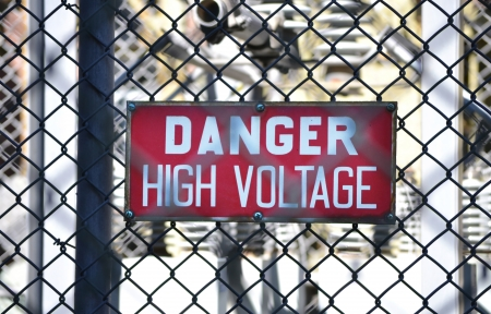 A red sign reading DANGER HIGH VOLTAGE at an electrical substation