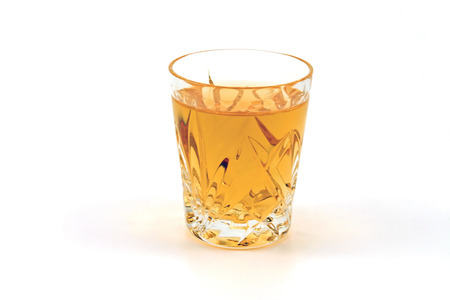 shooter drink: A shot glass of whiskey against a white background