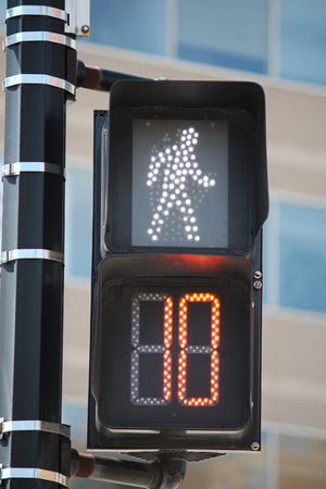 A pedestrian signal showing it is safe to cross for 10 more seconds