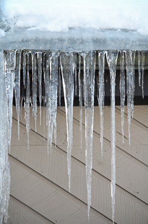 Icicles hanging off a roof in the sunlight Stock Photo