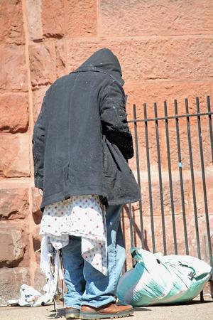 A homeless man outside a church on a sunny day
