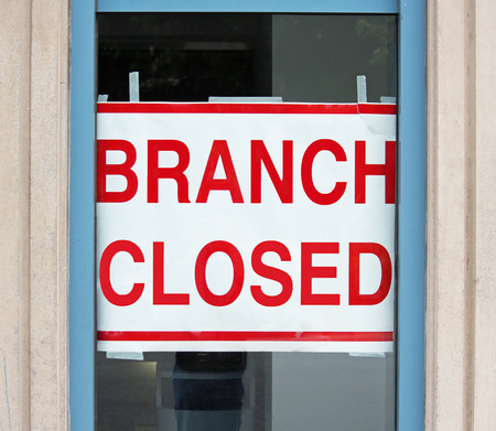bank branch: A sign in a store window reading Branch Closed