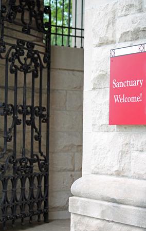 rood teken: Een rood bord buiten een kerk lezen Sanctuary Welkom! Stockfoto