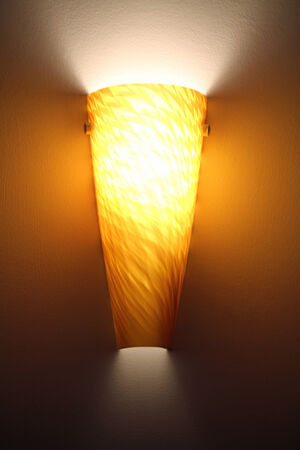 sconce: An indoor lamp lit against a dark wall