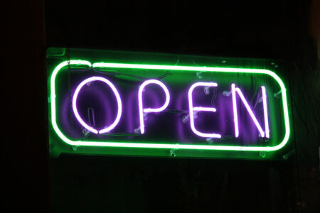 shop sign: An open sign in the window of a retail establishment
