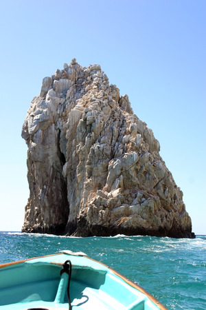 A rowboat approaching a rock formation at Los Arcos in Cabo San Lucas, Mexico