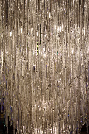 A glass chandelier with long hanging rods and beads Stock Photo