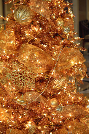 An artificial gold Christmas tree with lights and ornaments Stock Photo