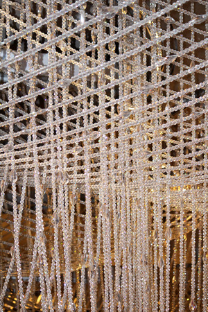 Many strands of crystals hanging in a geometric pattern