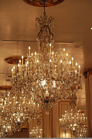 Many crystal chandeliers handing from a ceiling