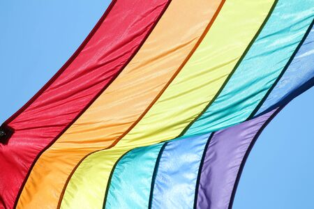 gay flag: Close Up of a gay pride flag against a clear blue sky