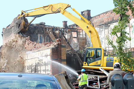 An excavator demolishing a damaged building Stock Photo