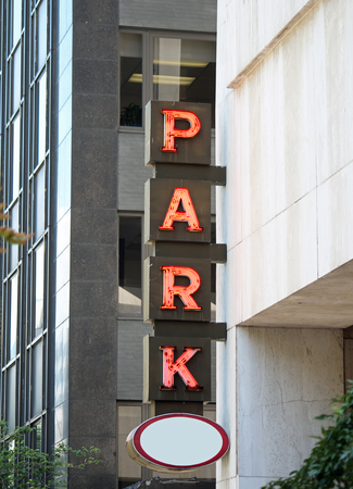 A red neon parking sign in a city