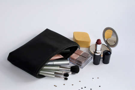 beautify: Black make up bag with assorted brushes lipstick,mirror & sponge Stock Photo