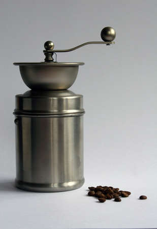 perk: Stainless steel coffee grinder with coffee beans on a grey background