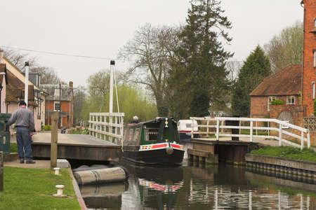 motoring: Narrow boat motoring through canal lock in village Stock Photo