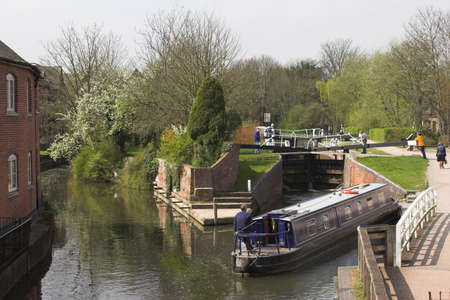 Blue narrow boat waiting to go through lock on canal Stock Photo