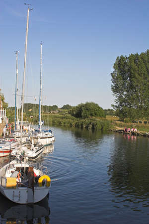 river scene with family having picnic on bank with yachts in river photo
