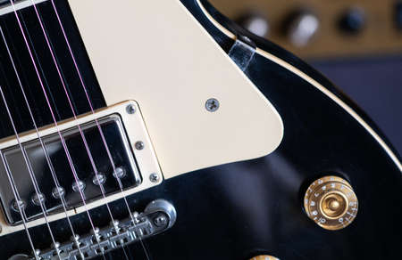 black Electric guitar body with silver pickups , chrome bridge and gold control knobs