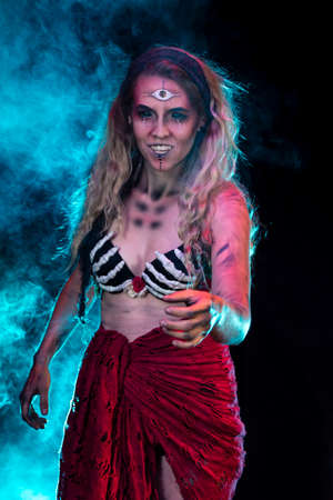 A female gypsy character. HalloweenHorror inspired with dark themes. Custom theatrical lighting and special effects makeup used. Blonde female model in skeleton hand bra and wrapped skirt.