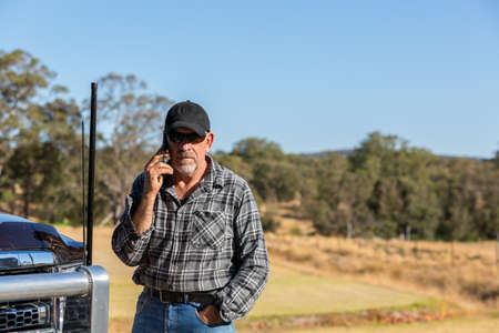 Man on mobile phone overlooking paddock, next to truck with antennas