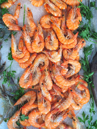 Seafood stall on a provencal market featuring raw tiger prawns and ready to eat shrimps Stock Photo