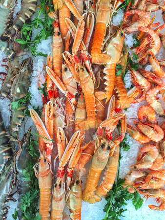 Seafood stall on a provencal market featuring raw tiger prawns and ready to eat shrimps and crayfish