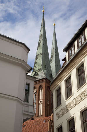 worshipping: View of Nikolaikirche (Church of St. Nicholas) through the buildings.  It is the oldest church in Berlin. Stock Photo