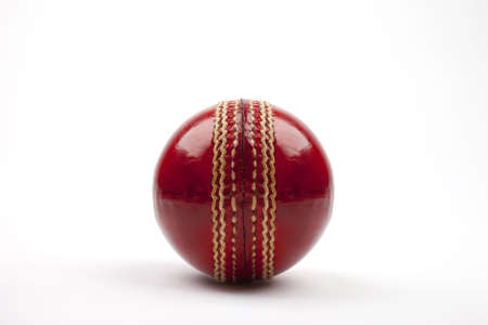 A Close-up shot of a red Cricket ball on white background. photo