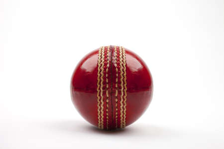 cricket game: A Close-up shot of a red Cricket ball on white background. Stock Photo