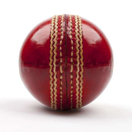 A Close-up shot of a red Cricket ball on white background.