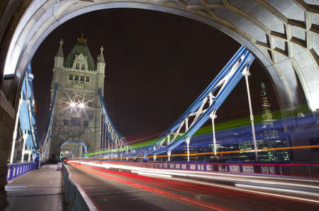 Traffic trails crossing Tower Bridge in London photo