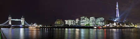 thames river: A panoramic view taking the sights of Tower Bridge, London Assembly Building, HMS Belfast and the Shard in London.