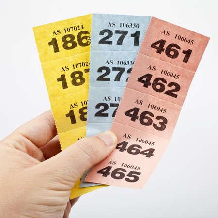 loteria: Mano que sostiene tres tiras de boletos de la rifa