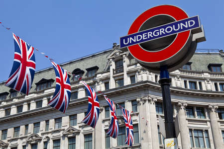 great britain: London Underground sign and Union Flags in London. Editorial