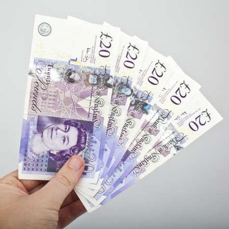 cash in hand: Mano que sostiene cinco billetes de 20.