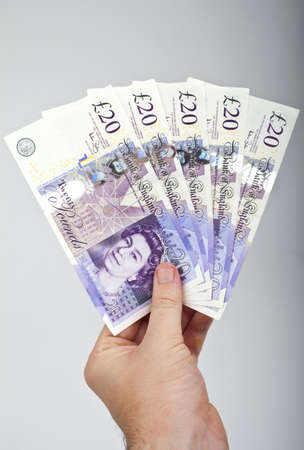 cash on hand: Hand holding five �20 notes.