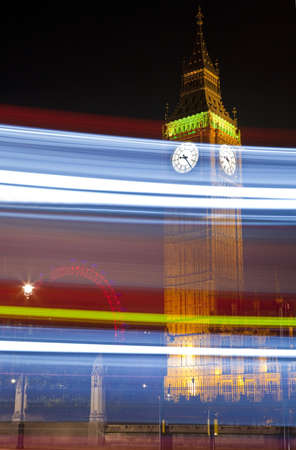 Light trails passing by Big Ben (Houses of Parliament).  The London Eye is in the background.